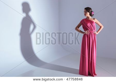 full length photo of a young beauty woman looking at her shadow from the studio wall while holding her hands on her hips. on a light gray background