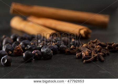 cloves cinnamon juniper berries Gyn tonic spices on black background