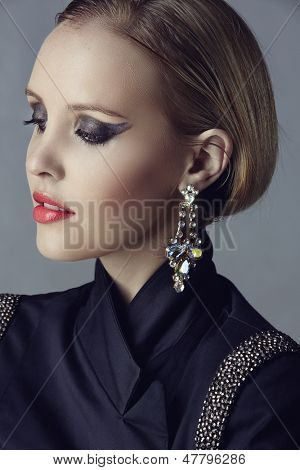 Portrait of beautiful blond woman with studio pulled back wearing diamante statement earrings and blazer with beads on studio background poster