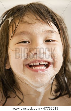 Little girl with soap suds on face
