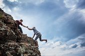 Man giving helping hand to friend to climb mountain rock cliff poster