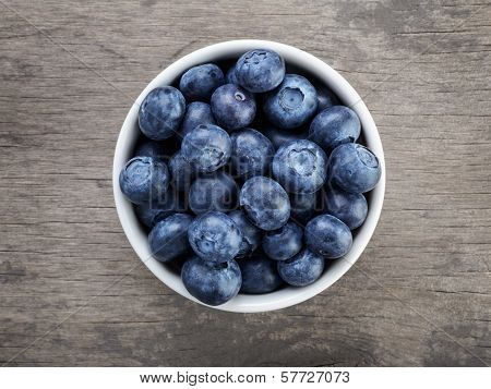 Fresh Blueberries In White Bowl On Wood Table