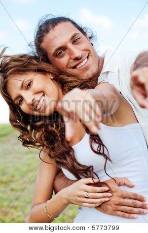 Happy Couple Pointing Towards Camera
