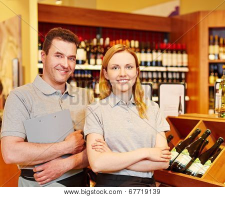 Happy store manager and smiling saleswoman in wine shop