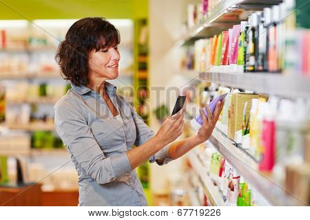 Elderly woman scanning barcode of cosmetics product in a drugstore