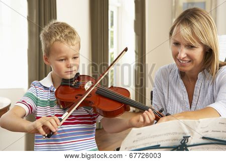Young boy playing violin in music lesson