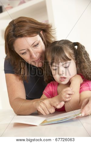 Mother and Downs Syndrome girl reading