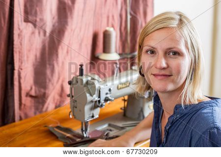 Smiling Blonde Woman At Sewing Machine