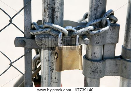 A Genuine Heavy Duty Pad Lock attaches a very strong carbon steel chain around a chain link fence to keep intruders out