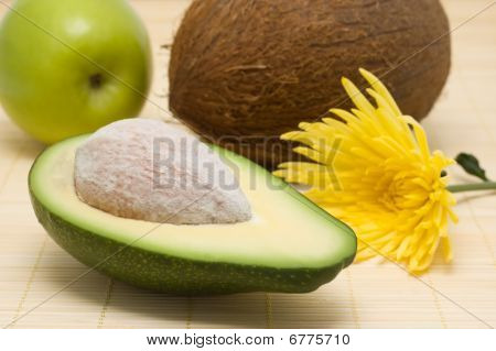 Avocado, Coco, Apple And Yellow Flowers On A Rug.