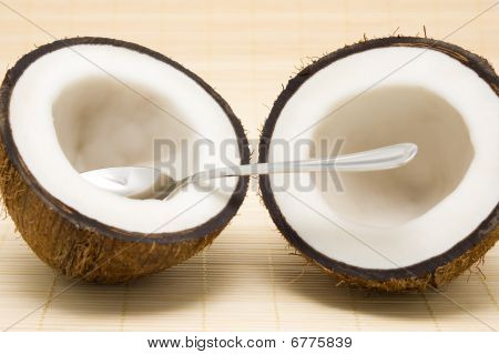 Two Halves Of A Coco With A Spoon On A Rug.