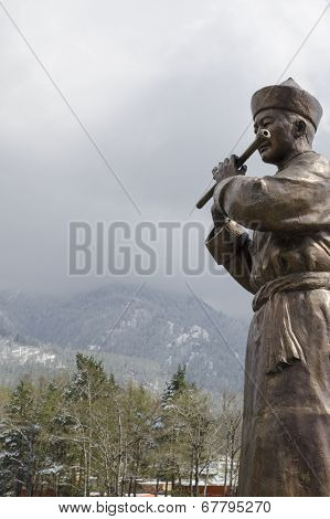 Sculpture of a man in the Buryat national dress with flute on the bridge over Kyngyrga river in Arsh