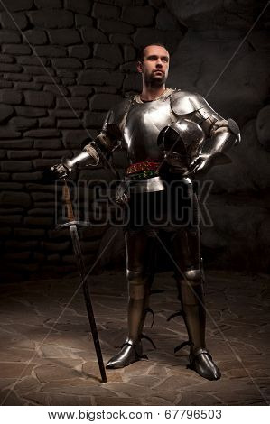 Medieval Knight posing with sword in a dark stone background