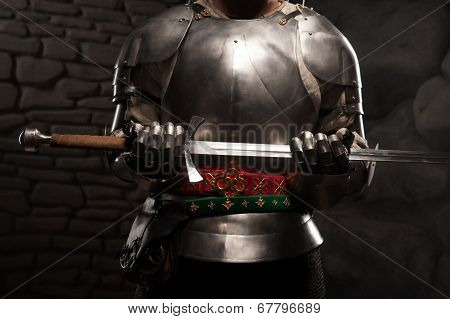 Closeup portrait of medieval knight in armor holding a sword
