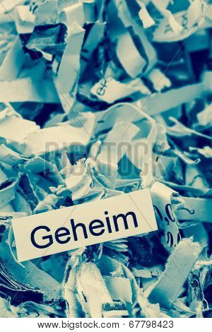 shredded paper tagged with secret, symbol photo for data destruction, secrecy and economic espionage