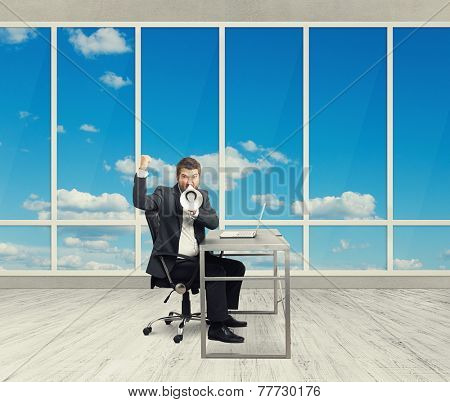 emotional businessman screaming with megaphone and looking at camera in the light office with big windows