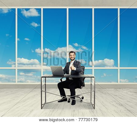 smiley successful businessman sitting at the table with laptop, showing thumbs up and looking at camera in the light office with big windows