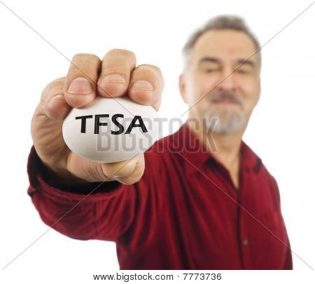 Mature Man Holds White Nest Egg With TFSA On It.