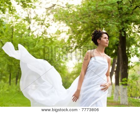 Young White Dressed Woman Walking In Spring Park