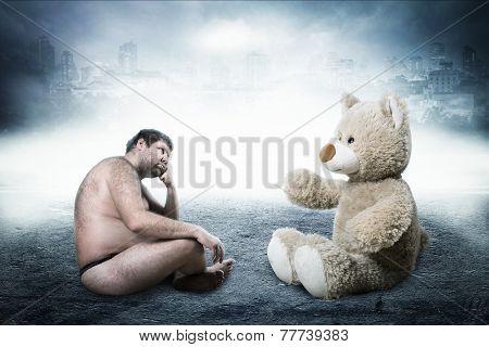 Strange naked man looks at toy bear