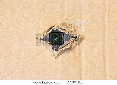 Hidden camera in torn hole in cardboard paper