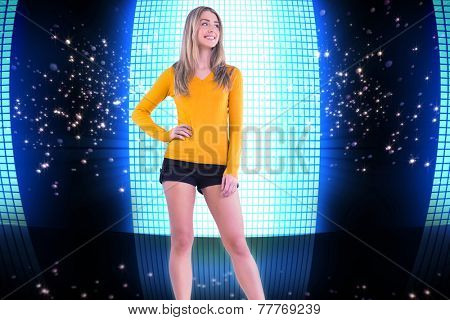 Stylish blonde smiling with hand on hip against glittering screen on black background