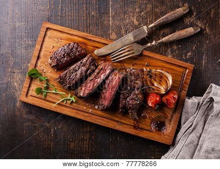 Sliced Medium Rare Grilled Beef Steak Ribeye With Grilled Onions And Cherry Tomatoes On Cutting Boar