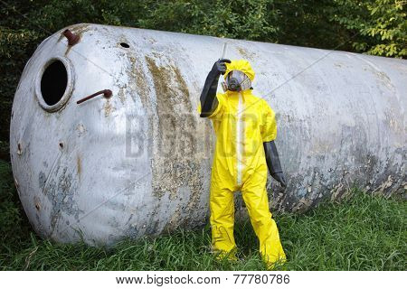 contamination - technician in protective coveralls ,mask, and gloves examining sample from large stainless tank