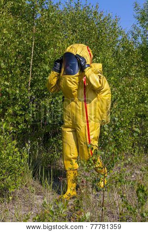 Man with briefcase in protective hazmat suit.