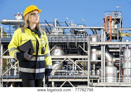 Woman, posing with a tablet and cb radio in front of a petrochemical installation as plant and safety officer