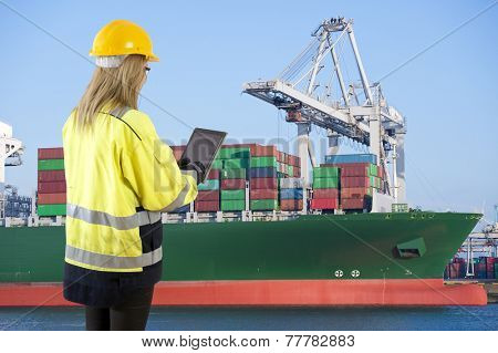 Female docker overlooking the unloading of a large container ship in an industrial harbor, carrying an electronic consignment note on her tablet poster