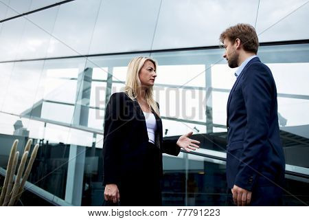 Boss and employee standing outside the office talking serious