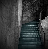 Spooky old stone interior staircase with rusty handrail poster