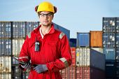 Logistics manager at a container transhipment plant, with an electronic tablet, and cb radio observing safety regulations poster