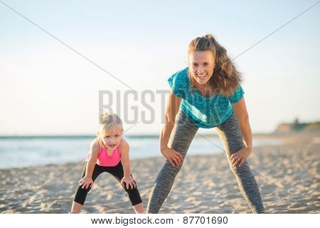 Healthy Mother And Baby Girl Workout On Beach In The Evening