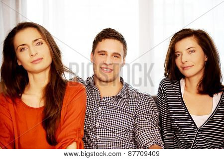 Sisters and brother sitting on the sofa. poster
