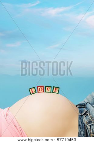 Letter boxes on pregnant woman belly