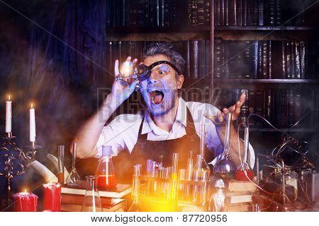 Portrait of a crazy medieval scientist working in his laboratory. Alchemist. Halloween.