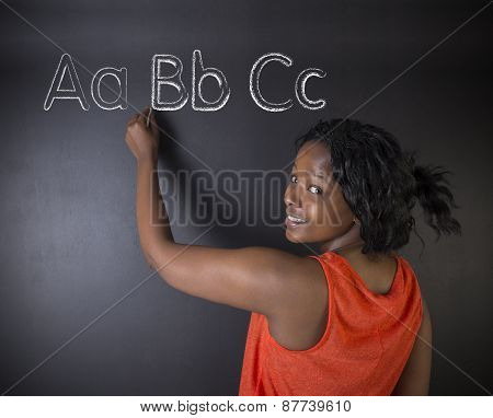 South African Or African American Woman Teacher Or Student Learn Alphabet Write Writing