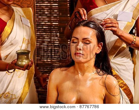 Young woman having head massage in ayurveda spa treatment.
