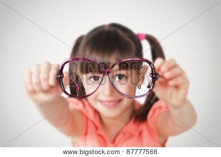 little girl holding eyeglasses health eyesight concept. Soft focus poster
