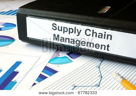 Graphs and file folder with label supply chain managment.