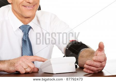 Mature businessman measuring blood pressure.