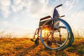 Empty wheelchair on the meadow at sunset. Miracle concept. Healed person raised and went away poster