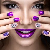 Beautiful girl with a bright evening make-up and manicure with rhinestones. Nail design. Beauty face. Picture taken in the studio on a black background. poster