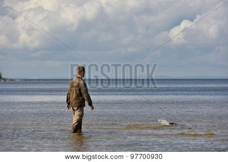 VALAAM ISLAND, RUSSIA - JULY 29, 2015: Vyacheslav Alekseev releases the Ladoga ringed seal into the lake Ladoga. Animal was cured in the Center of study and conservation of marine mammals