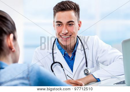 Medical Doctor Attending Female Visit At Desk.
