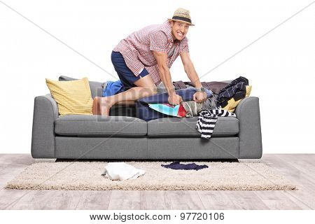 Young man packing a lot of clothes into one suitcase and looking at the camera isolated on white background