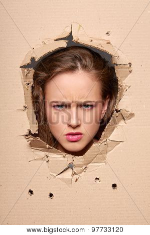 Displeased girl peeping through hole in paper poster