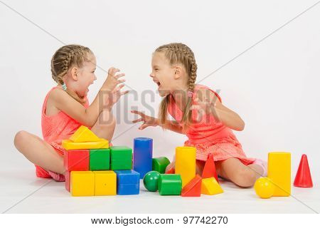 Two Girls Frighten Each Other By Playing With Blocks
